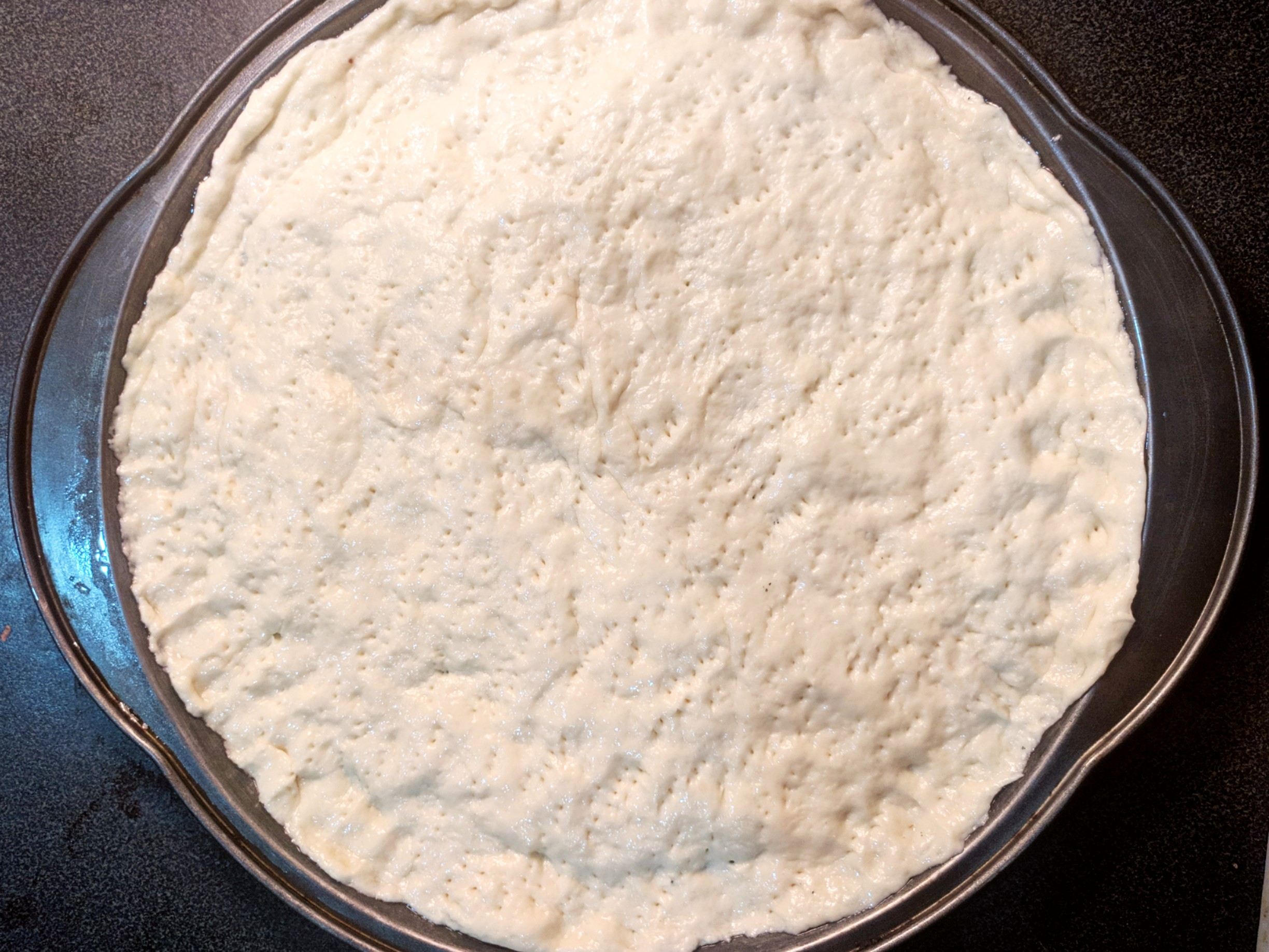 spreading pizza dough